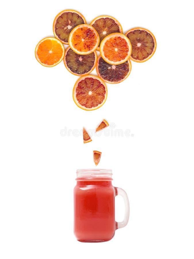 与新鲜的血液橙汁过去的玻璃站立在白色背景的许多血橙切片下 免版税库存照片