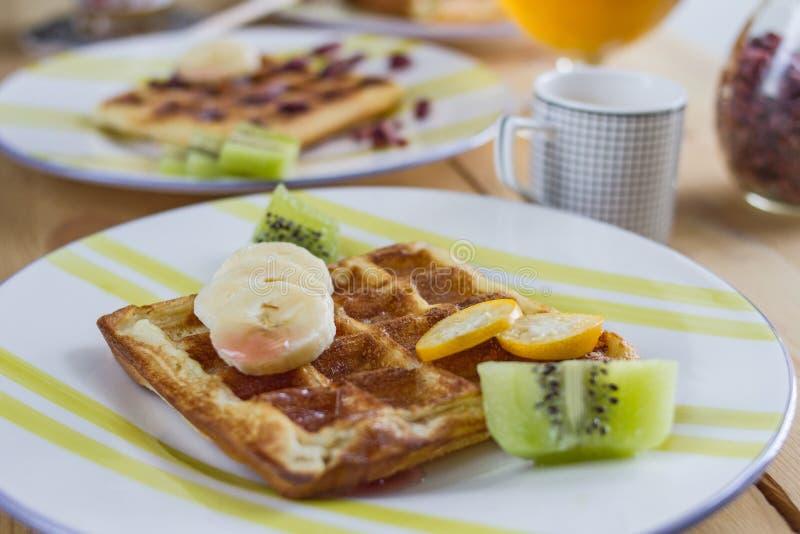 与新鲜的香蕉、猕猴桃、金桔和枫蜜片断的开胃油煎的金黄比利时华夫饼干在一块镶边陶器板材 库存图片