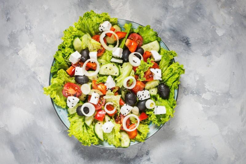 与新鲜蔬菜、希腊白软干酪和橄榄的传统希腊沙拉在具体背景 顶视图 库存照片