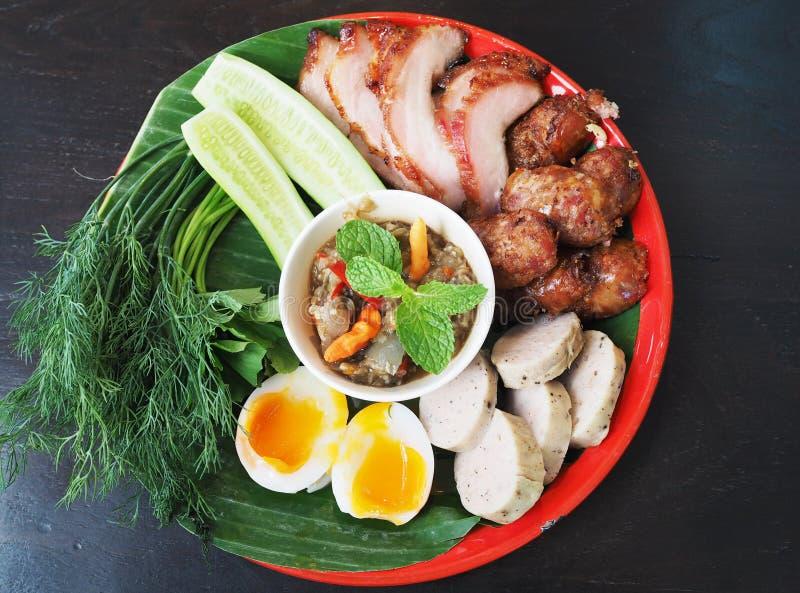 与新鲜蔬菜、熟蛋、烤猪肉和辣椒酱的Isaan泰国食物集合 免版税库存照片