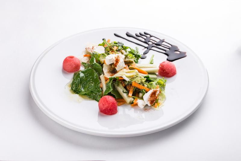 与新鲜蔬菜和奶油奶酪的沙拉在白色背景隔绝的白色板材 库存图片
