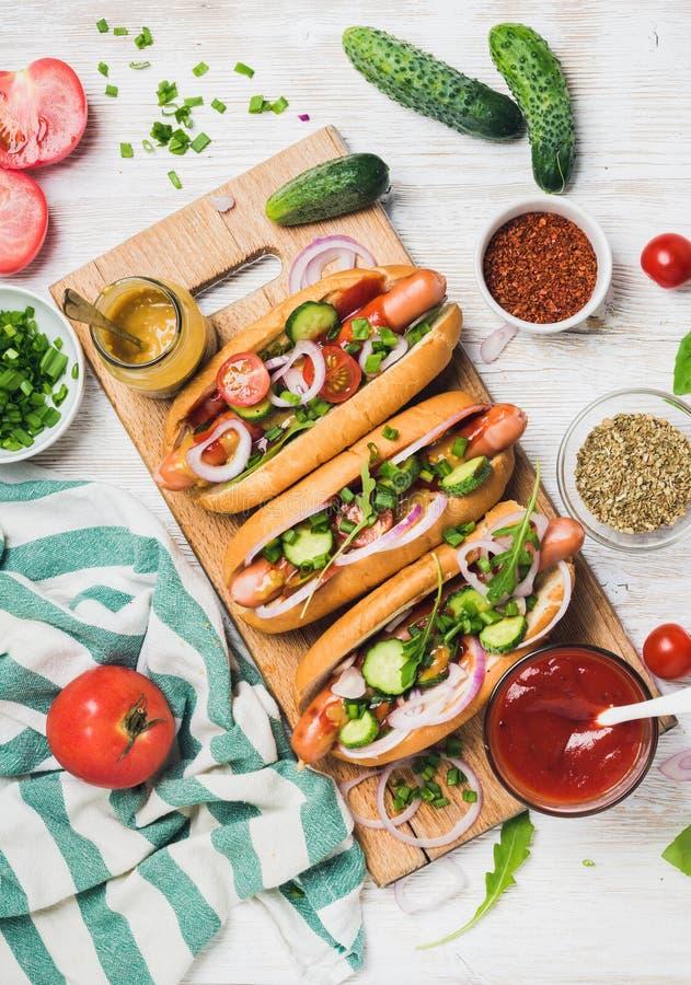 与新鲜蔬菜和香料的自创热狗在白色背景 库存照片