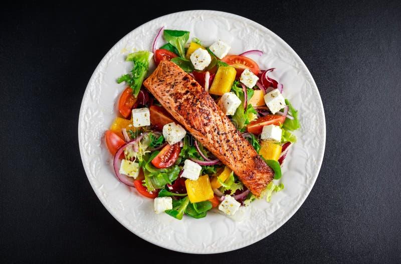 与新鲜蔬菜沙拉,希腊白软干酪的油煎的鲑鱼排 概念健康食物 库存照片