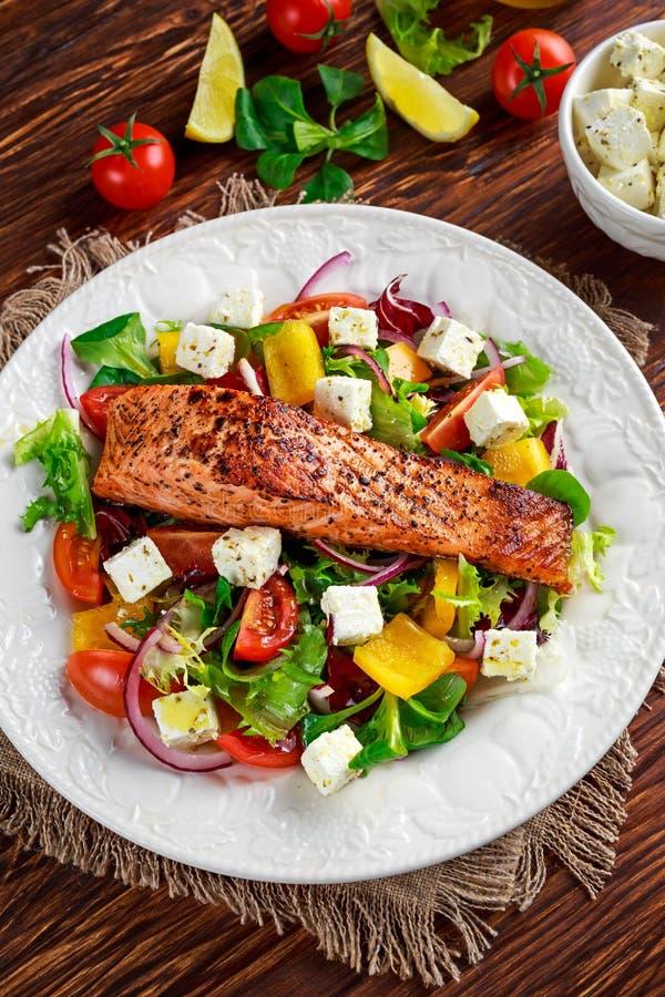 与新鲜蔬菜沙拉,希腊白软干酪的油煎的鲑鱼排 概念健康食物 库存图片