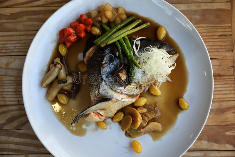 与新鲜蔬菜的三文鱼顶头tari yaki调味汁在木桌上 库存照片