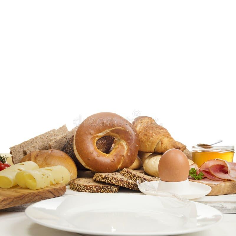 与新鲜面包卷、百吉卷、鸡蛋、香肠和乳酪的早餐 免版税库存照片