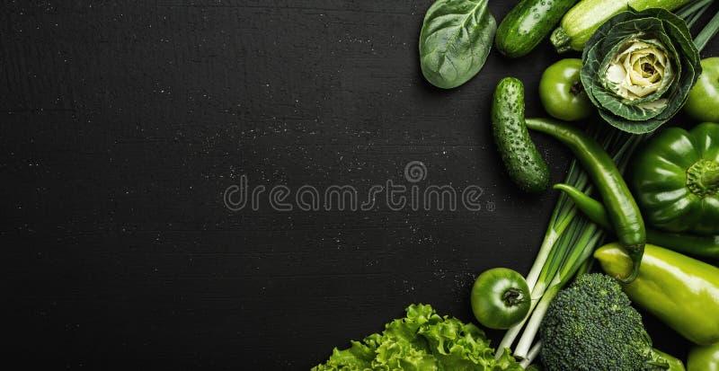 与新鲜,绿色菜的健康食物概念在黑石桌上 免版税库存图片