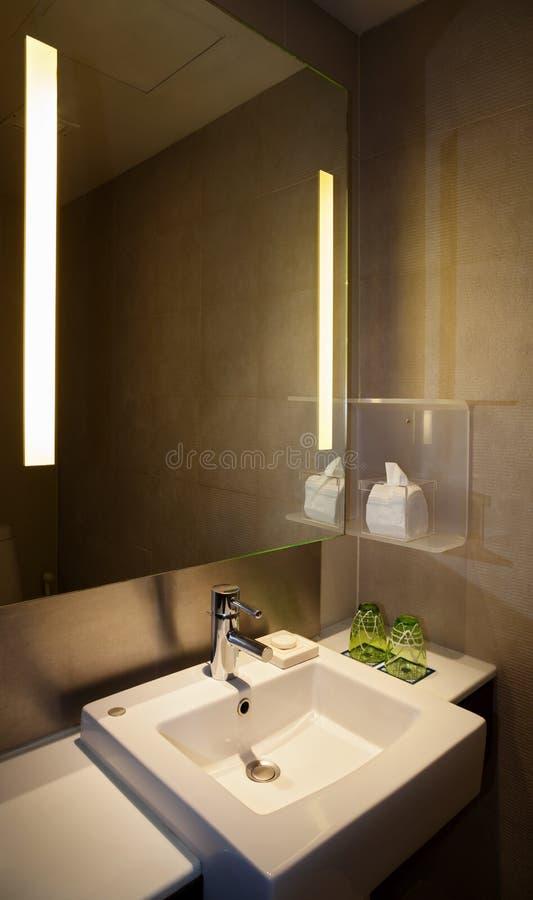 与方形的水槽的水龙头在与有启发性镜子和布朗瓦片的现代WC 库存图片
