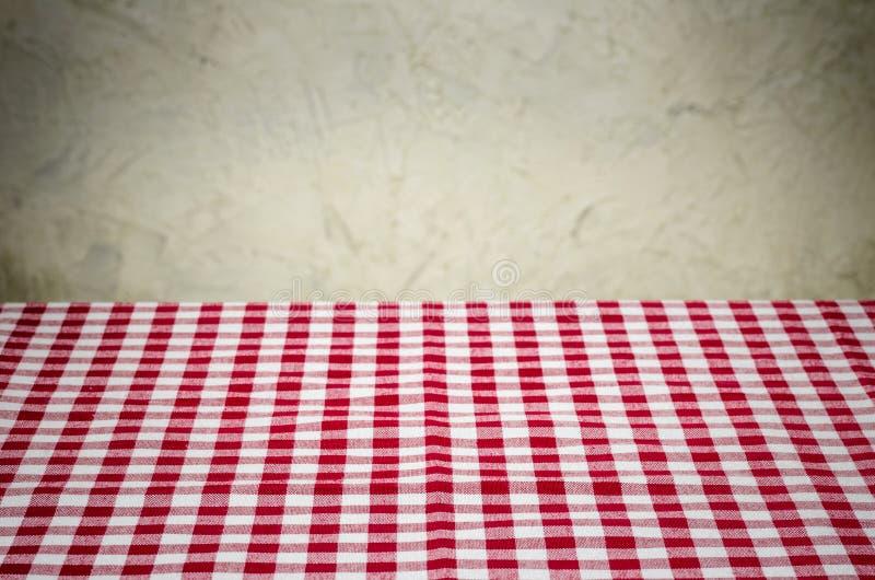 与方格的桌布和土气墙壁的背景 免版税库存图片