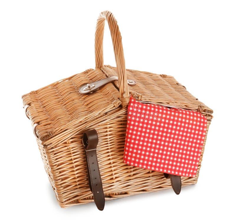与方格的桌布的闭合的柳条野餐篮子 库存图片