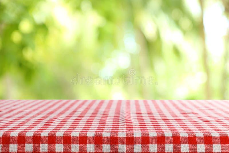 与方格的红色餐巾的空的桌在绿色被弄脏的背景 库存照片