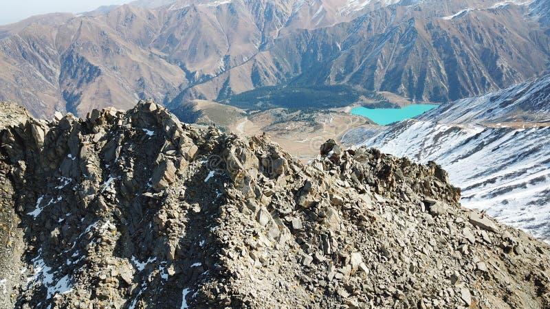 与旁边射击的一个岩石峰顶在寄生虫 山湖绿松石的看法 免版税图库摄影