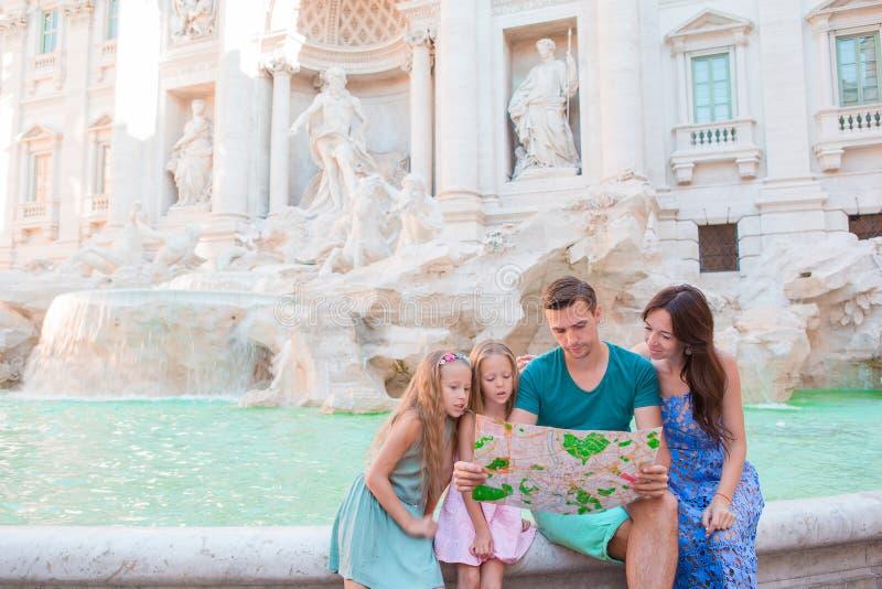 与旅游地图的家庭在Fontana di Trevi,罗马,意大利附近 愉快的父亲和孩子享受意大利假期假日  免版税库存图片