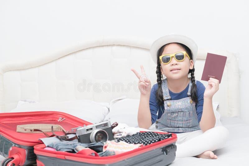 与旅行辅助部件服装的逗人喜爱的女孩展示护照 库存图片