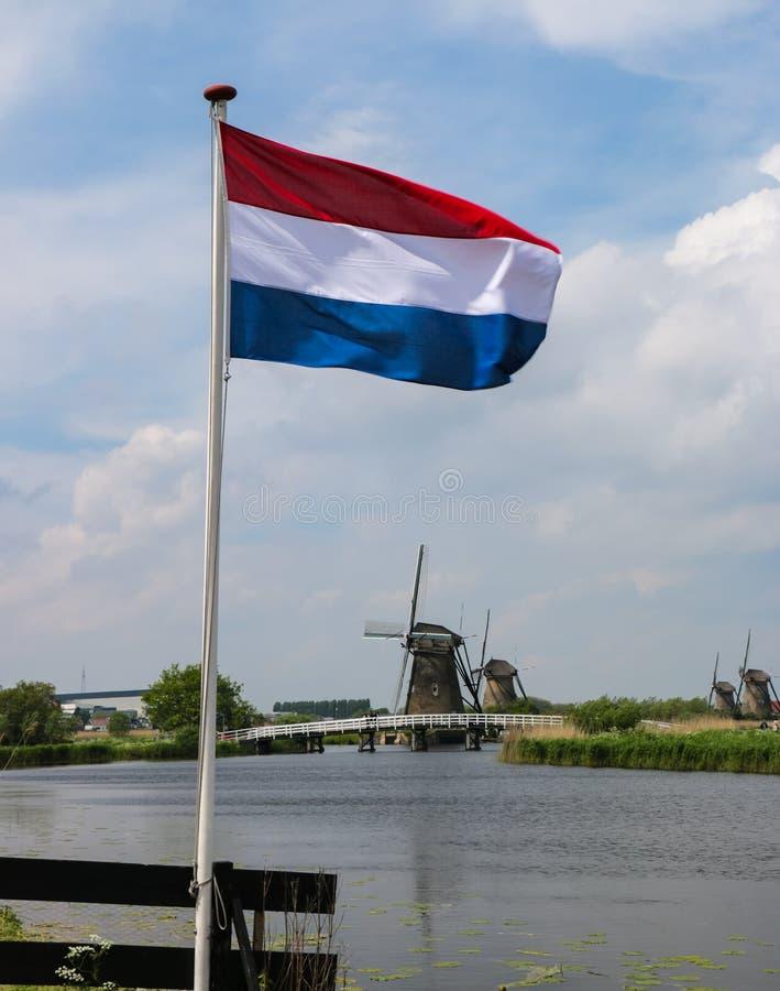 与旗子、运河和风车的精华荷兰照片 免版税库存照片