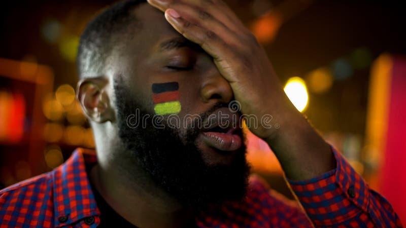 与旗子的失望的德国足球迷在做facepalm,队丢失的面颊 库存照片