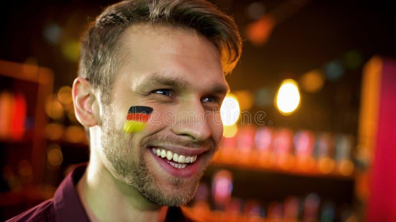 与旗子的快乐的德国足球迷在面颊愉快为队计分的目标,胜利 库存图片