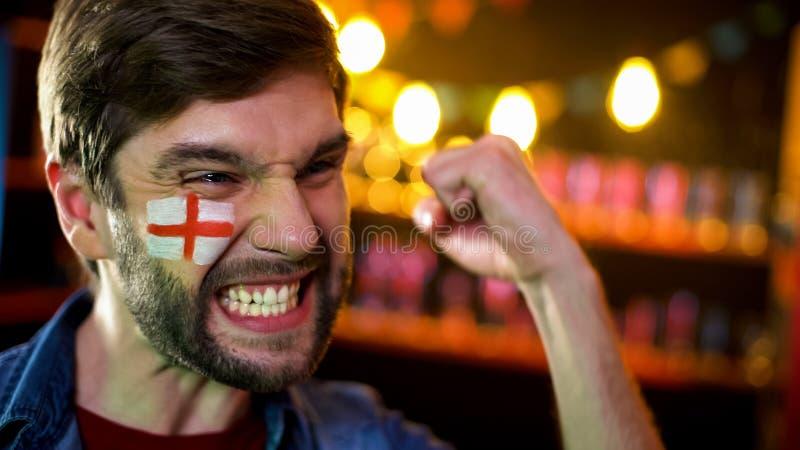 与旗子的快乐的英国足球迷在是做姿态,队赢得的面颊 免版税库存图片