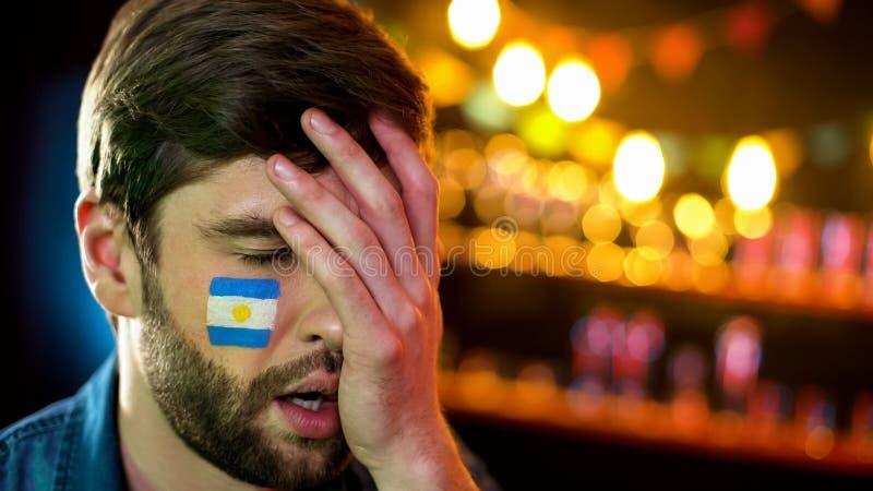 与旗子的阿根廷足球迷在做facepalm的面颊,怏怏不乐对于损失 免版税库存照片
