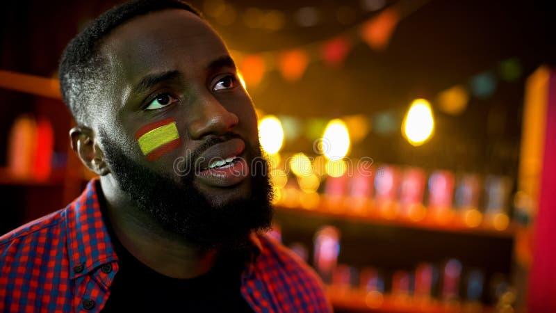 与旗子的黑西班牙足球迷在失望的面颊,国家队丢失 免版税图库摄影