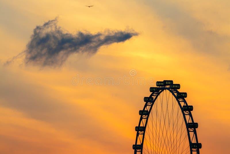 与日出早晨天空云彩的新加坡飞行物 库存照片