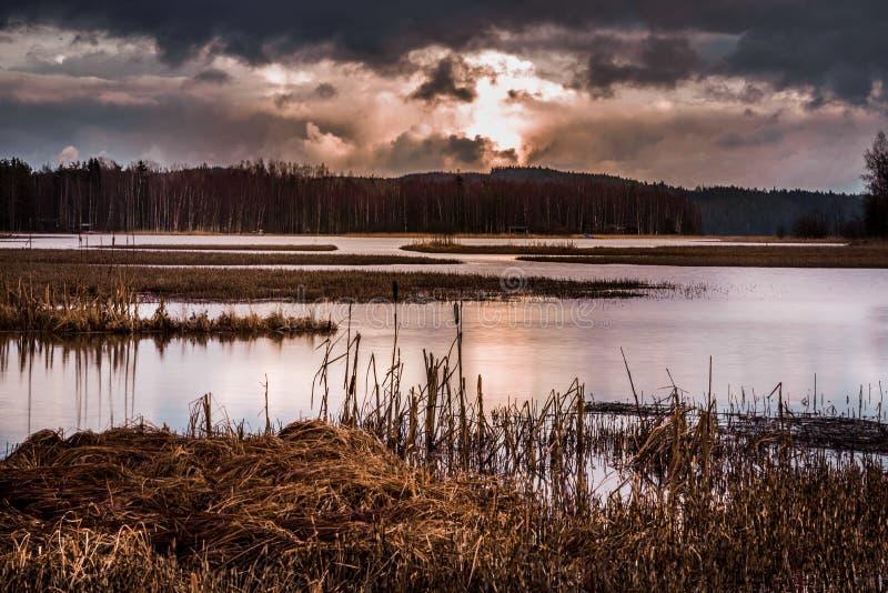 与日出的风雨如磐的风景湖边视图 免版税图库摄影