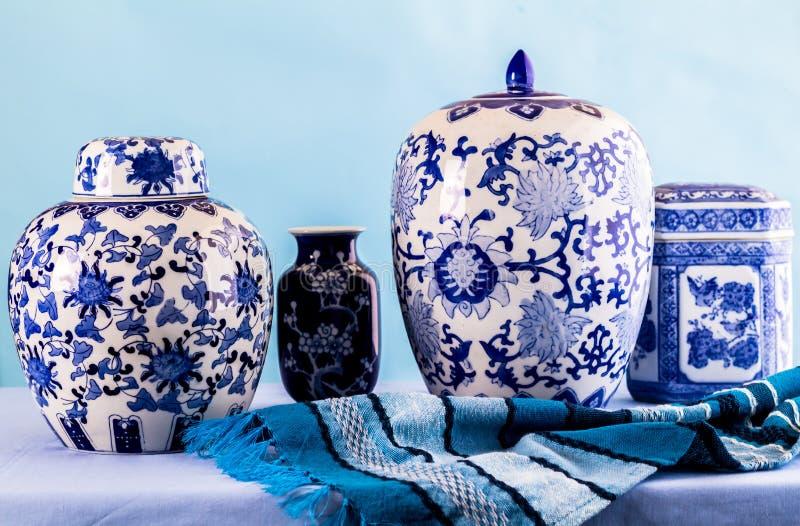 与日本蓝色和白色姜瓶子和花瓶的静物画在反对蓝色背景的蓝色 免版税库存照片