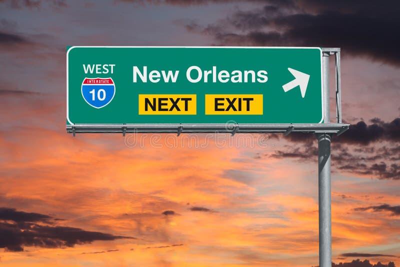 与日落天空的新奥尔良路线10高速公路下个出口标志 库存图片