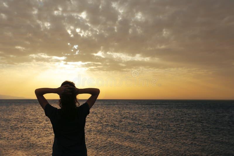 与日落的妇女剪影 图库摄影