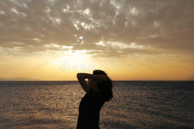 与日落的妇女剪影 免版税库存照片