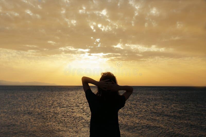 与日落的妇女剪影 库存图片