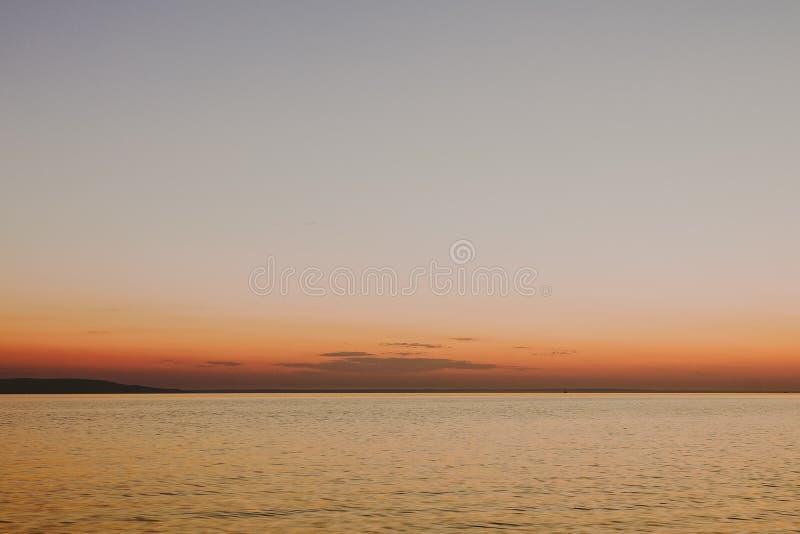 与日落的柔滑的光滑的水在背景中 免版税库存照片