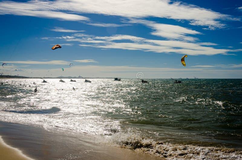 与日落的被曝光过度的作用与风筝冲浪者 库存照片