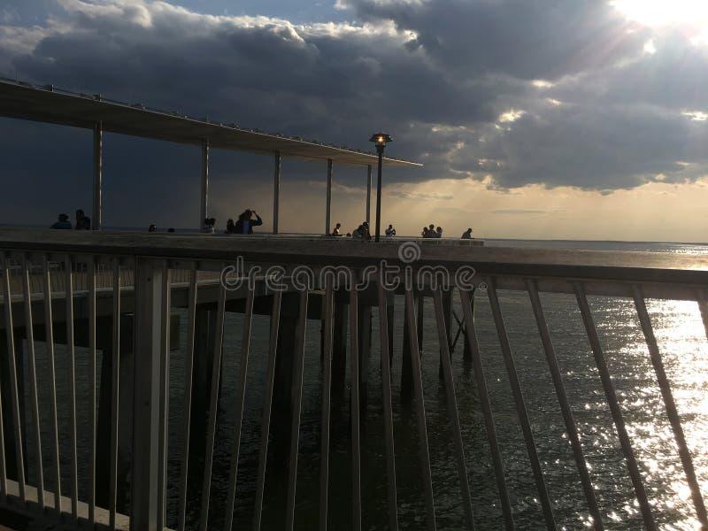 与日落的风雨如磐的云彩在码头和海洋 库存图片