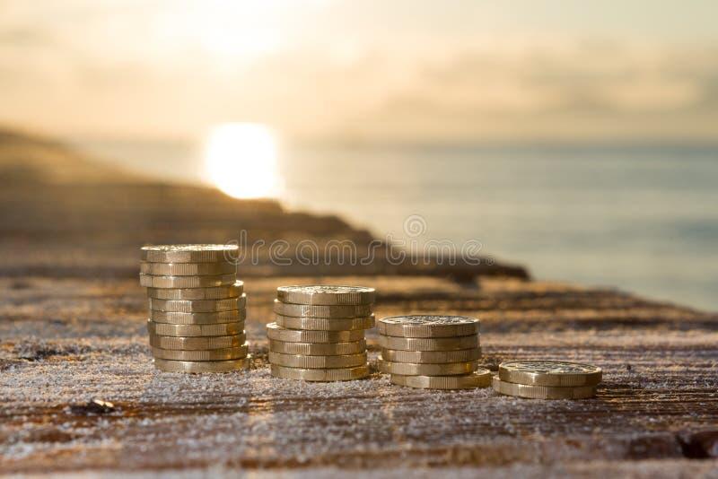 与日落的1英镑硬币堆在跳船金钱 库存图片