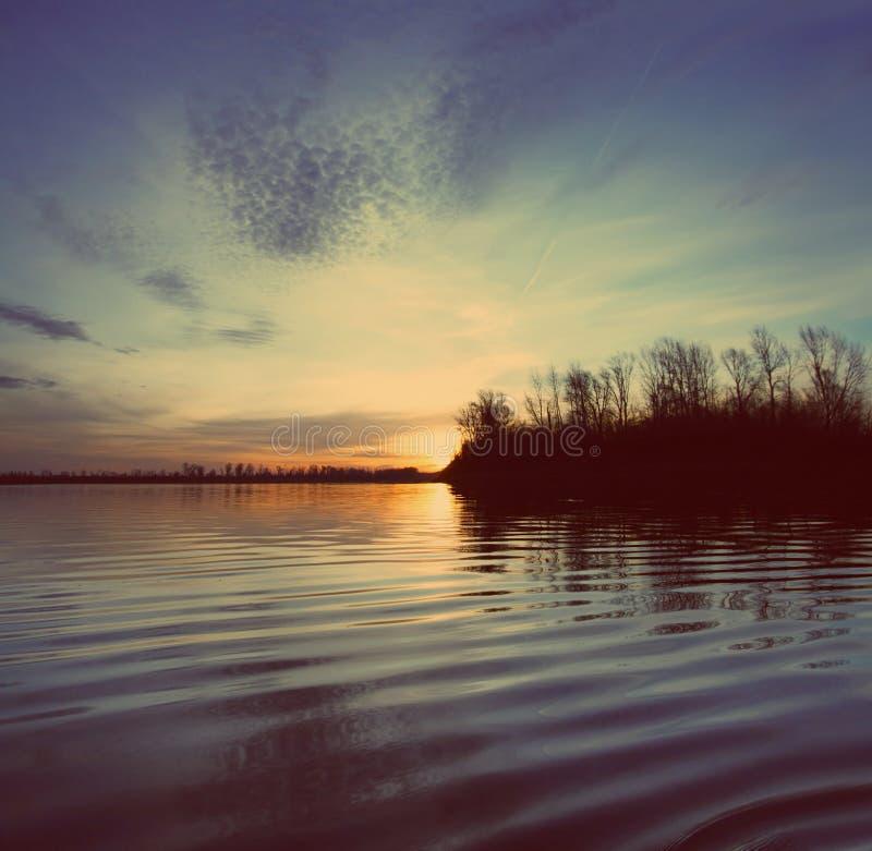 与日落-葡萄酒减速火箭的样式的河风景 免版税库存图片