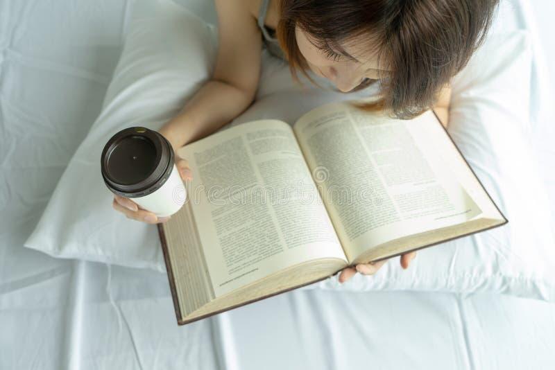 与早晨咖啡杯的年轻女人看书在卧室在家 亚洲说谎在与枕头的舒适床上的女孩饮料茶顶视图 免版税图库摄影