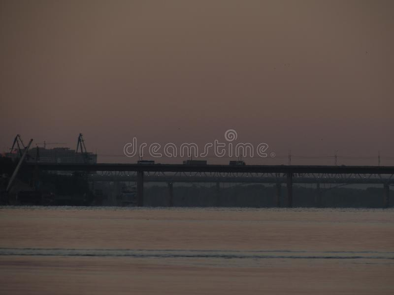 与早晨桥梁的黑等高的黎明都市风景反对天空和河的 库存图片