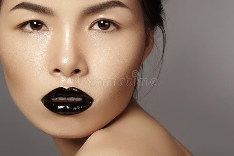 与时尚嘴唇的特写镜头画象亚洲模型化妆,干净的皮肤 秀丽与黑唇膏构成的万圣夜样式 免版税库存照片