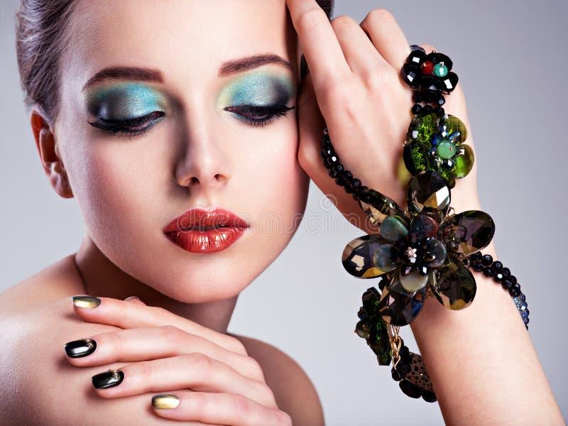 与时尚绿色构成的美丽的妇女在h的面孔和首饰 免版税库存图片