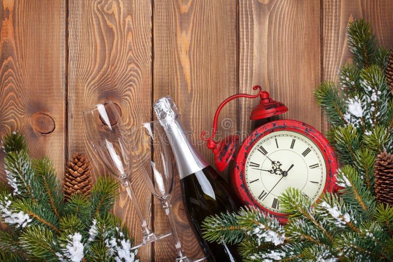 与时钟、香槟和雪冷杉t的圣诞节木背景 免版税库存照片
