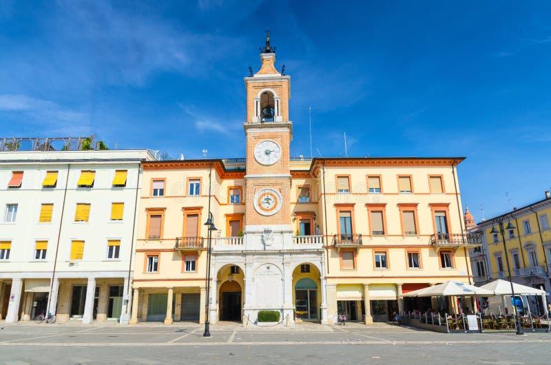 与时钟的传统建筑和在广场特雷Martiri的钟楼三个受难者在老历史市中心里米尼摆正 库存图片