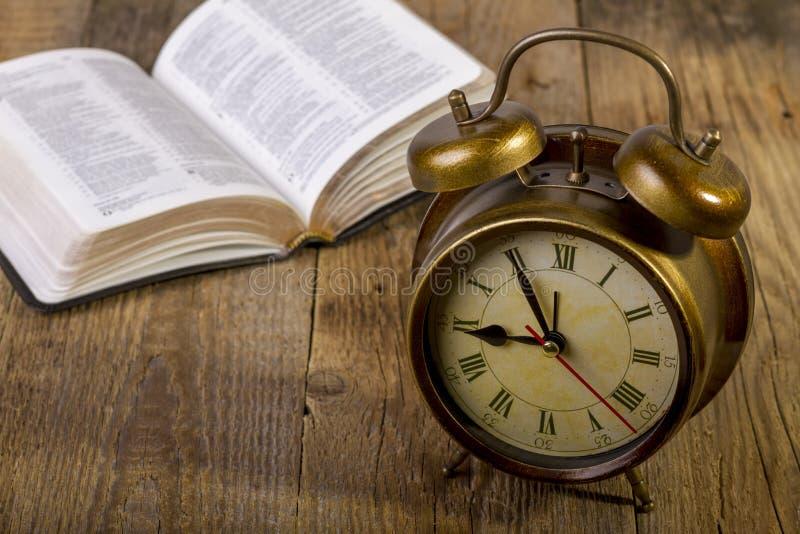 与时钟的圣经在木头 免版税库存图片