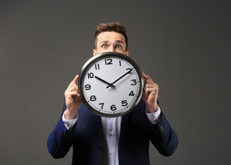 与时钟的成功的商人在黑暗的背景 E 免版税库存照片