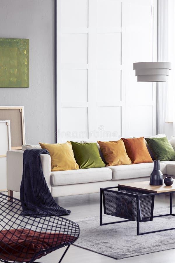 与时髦的咖啡桌和大舒适的长沙发的垂直的图o典雅的客厅内部有五个五颜六色的枕头的,真正 免版税库存照片