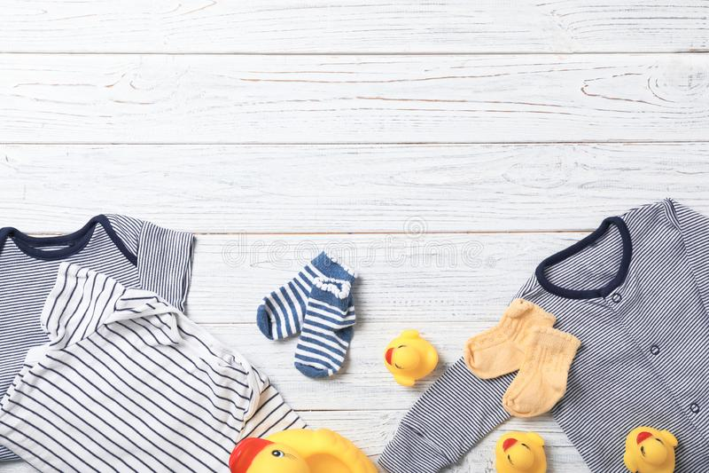 与时髦的婴孩衣裳和玩具的平的被放置的构成在木背景 库存照片