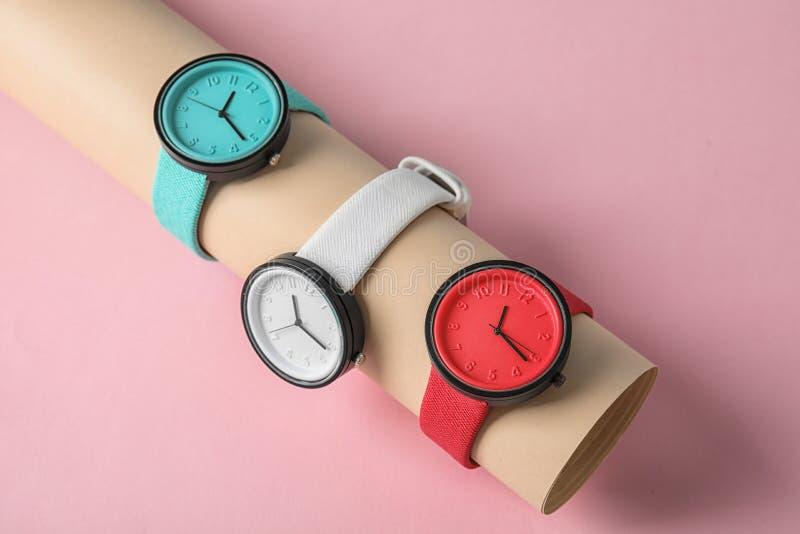 与时髦的手表的汇集的持有人在颜色背景的 免版税库存图片