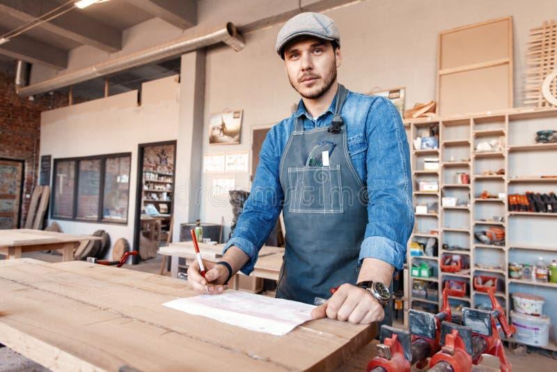 与时髦的盖帽工作的成功的英俊的商人在木匠业方面 免版税图库摄影