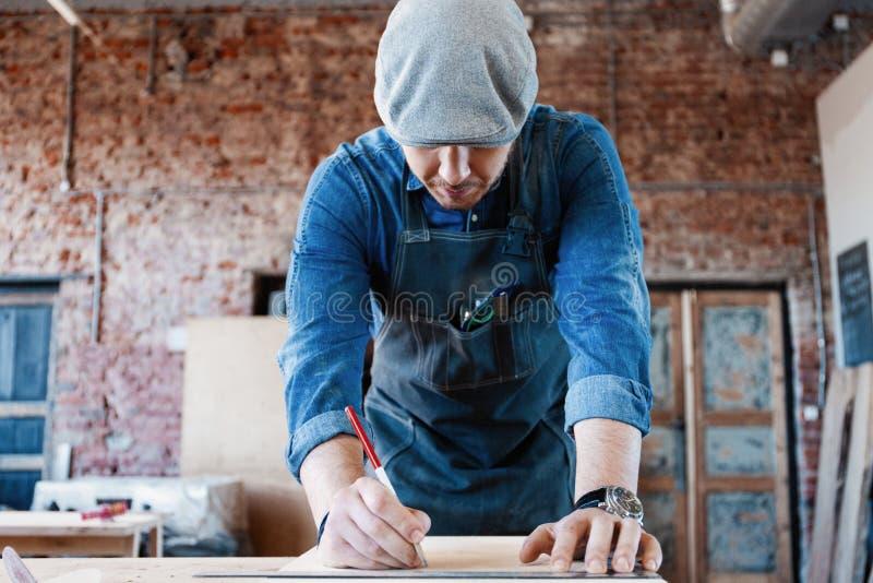 与时髦的盖帽工作的成功的英俊的商人在木匠业方面 免版税库存照片