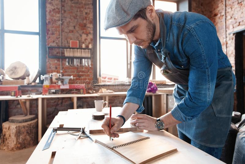 与时髦的盖帽工作的成功的英俊的商人在木匠业方面 免版税库存图片